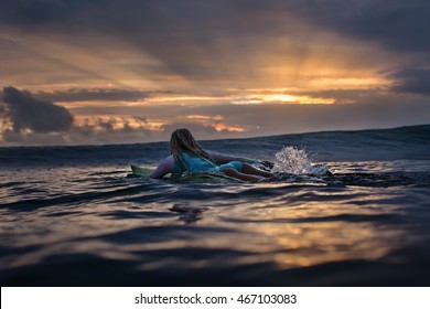 Beautiful Sunset in Ocean with surfing girl moving with surf board on water surface. Vibrant seascape in tropical waters