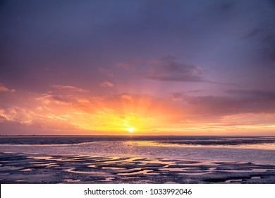 Beautiful sunset with the oceans tide coming in and large flocks of wild birds. Orange and purple skies light up the  East coast in Norfolk England famous for its wildlife and nature.