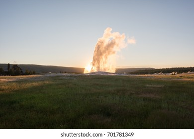 Beautiful sunset with Old Faithful Geyser erupting at Yellowstone National Park in Wyoming. Old Faithful was the first geyser in Yellowstone National Park to be named.