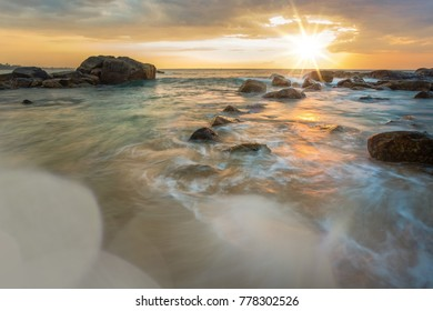 Beautiful sunset on the beach of Srilanka. Romantic atmosphere with long exposure capture. Sun and lense effects. Moving water and waves. Great ocean.