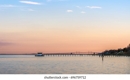 A beautiful Sunset on the Chesapeake Bay in Maryland with Bay Bridge, boathouse and lighthouse