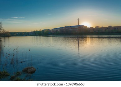 Beautiful sunset on the Knazal lake on the background of a large old weaving factory, the city of Yuzha, Ivanovo region, Russia.