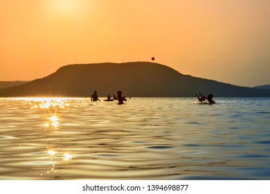 Beautiful sunset on the Lake Balaton with people bathing in water and behind them is the Badacsony Mountain.