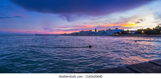 Beautiful sunset on Lido Di Jesolo beach – panoramic view from the pier to the sea with expressive sky and clouds in purple, purple and orange colors, summer evening, Veneto region, Italy