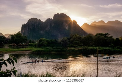 Beautiful sunset on the Nam Song river in Vang Vieng, Laos, crossed by long-tailed boats
