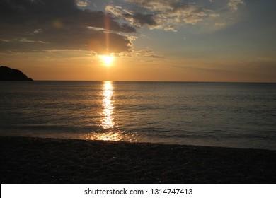 Beautiful sunset on Petani beach on the Kefalonia Island (Ionian Island) in Greece. Amazing Landscape. Summer, sea, waves and clouds