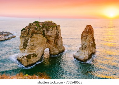 Beautiful sunset on Raouche, Pigeons' Rock. In Beirut, Lebanon.Sun and Stones are reflected in water.dense clouds in the sky.warm summer evening in the Mediterranean Sea.