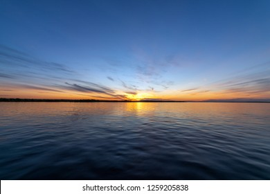 Beautiful sunset on the river. Summer sunset or sunrise landscape with golden light in Yakutia, Republic of Sakha, Russia. Riverscape taken from a ferry on river Lena. - Image