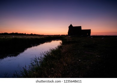 beautiful sunset on Romney Marshes Kent UK with silhouette of 13th century Fairfield church with reflections in stream