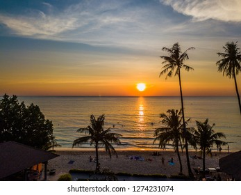 Beautiful sunset on the sandy beach of Thailand with huge palm trees and blue sky. The sea waves when the sum reaches the horizon.