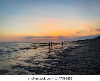 Beautiful sunset on the surf beach Batu Bolong in Canggu on Bali island, silhouettes of walking people and surfers