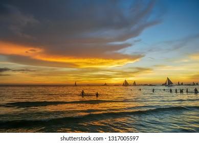 Beautiful sunset over bay at Sabang Puerto Galera of Oriental Mindoro, Philippines near Isla Verde Passage and Manila. Sunset Silhouettes. Amazing tropical sunset. Seascape during sunset.