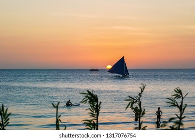 Beautiful sunset over bay at Sabang Puerto Galera of Oriental Mindoro, Philippines. Yacht sailing against sunset. Yachting tourism - maritime evening walk. Romantic trip on yacht during the sea sunset