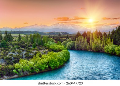 Beautiful sunset over the bend of the river Clutha with Southern Alps peaks on the horizon, New Zealand