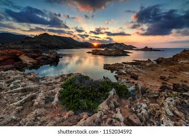 Beautiful sunset over Cala Pregonda in Menorca, Spain. Bibrant colors, orange clouds and vegetation in the frame