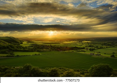 Beautiful sunset over countryside landscape of rolling hills with sun beams piercing sky and lighting hillside