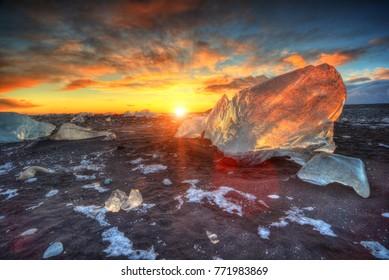 Beautiful sunset over famous Diamond beach, Iceland. This sand lava beach is full of many giant ice gems, placed near glacier lagoon Jokulsarlon.