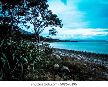 Beautiful sunset over the Hauraki Gulf, with ocean and islands in the distance and trees and beach silhouetted in the foreground. Taken on the Coromandel Peninsula, New Zealand.