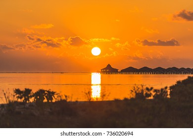 Beautiful sunset over the horizon. Water villas on the background of bright sunset.