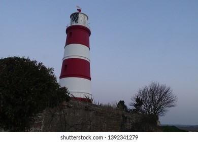 Beautiful sunset over iconic red and white lighthouse in Happisburgh, North Norfolk, England, UK
