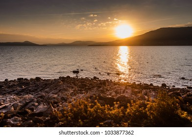 Beautiful sunset over a lake with rocky coast in front and mountains in the background. Lago Maggiore in Italy.