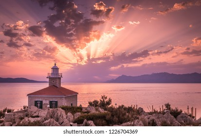 Beautiful sunset over Mediterranean sea with lighthouse in the foreground in Makarska, Croatia