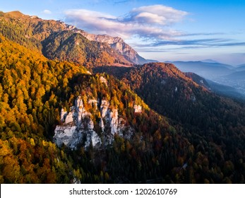 Beautiful sunset over the mountain forest in autumn season, October. Colors of the forest in the sunset light from above. Aerial view over the colorful forest of autumn season in the mountains. Sinaia