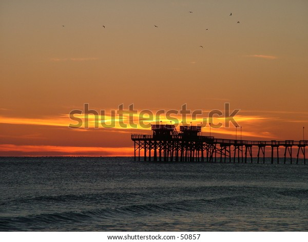 Beautiful Sunset over a Pier with Sea Gulls in flight taken on Atlantic Beach, NC