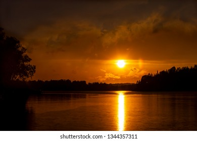 Beautiful sunset over a remote northern Minnesota fishing lake, silhouetting the shoreline trees, with smoke from fires in Canada, rolling over the lake and sun rays reflecting off the water.