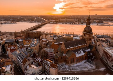 Beautiful sunset over Riga old town during cold winter day. View from the main Domes cathedral on the river Daugava, national library and the old town.