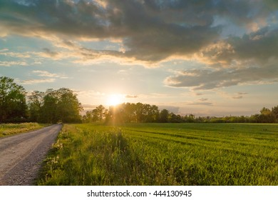 Beautiful sunset over a road crossing a meadow