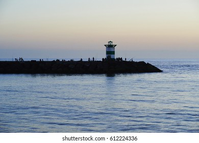 Beautiful Sunset over rocks and lighthouse with silhouettes of people (locals, fishermen, tourists). Scheveningen coastline, The Hague, Netherlands
