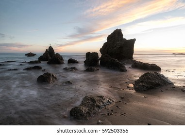 beautiful sunset over rocks in Pacific Ocean at the El Matador state beach, California