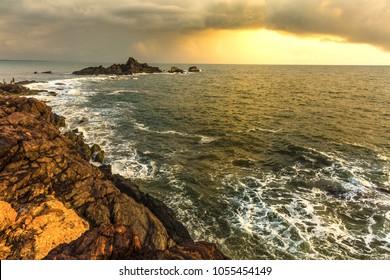 Beautiful sunset over the rocky beach of Gokarna called OM beach in Karnataka, India. This beach is in the shape of OM / AUM. Serene peaceful coast, golden hour landscape, cloudy horizon, Romantic
