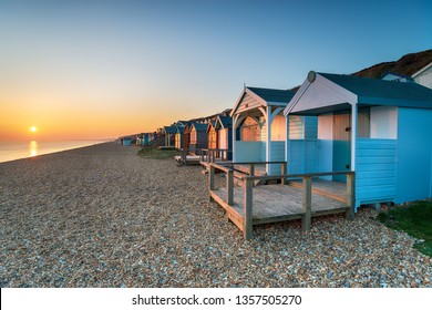 Beautiful sunset over a row of colourful beach huts at Milford on Sea on the Hampshire coast