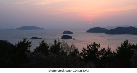 A beautiful sunset over a sea and islands. Taken in Tongyeong, South Korea, but suitable to illustrate coastal communities, vacations, holidays, nature, relaxing places, parks or coastal living.