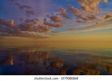 Beautiful sunset over sea with reflection in water, majestic clouds in the sky.
