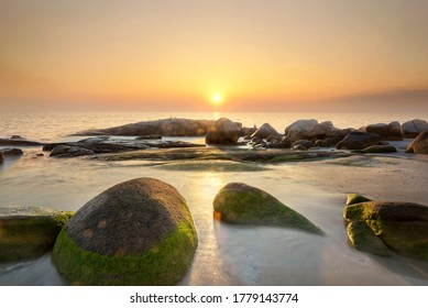 Beautiful sunset over sea with rocks covered by green moss