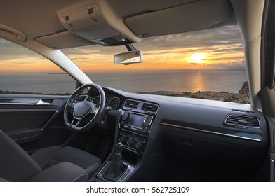 beautiful sunset over the sea seen from the inside of a car