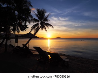 Beautiful sunset over the sea  and silhouette beach umbrella and chairs on the beach.