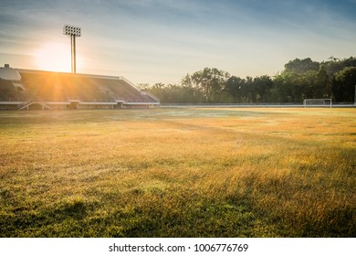 Beautiful sunset over the sport field in stadium. Football arena with green grass and rays of sunlight. Soccer championship tournament background concept.