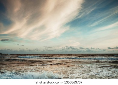 Beautiful sunset over wavy Baltic sea. Soft blue color and white yellow clouds on the sky.