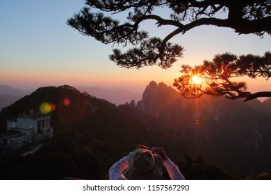 Beautiful sunset and pine tree silhouette in Huangshan Mountain, Huangshan City, Anhui Province, China.