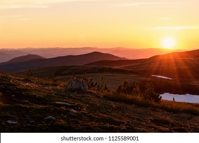 Beautiful sunset with rays over the contours of mountains with stones, small cedars and snow in the foreground
