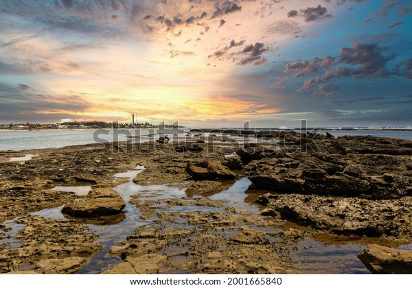 Beautiful Sunset at a reef with a bird in the water, Barra de São Miguel, Alagoas, Brazil.