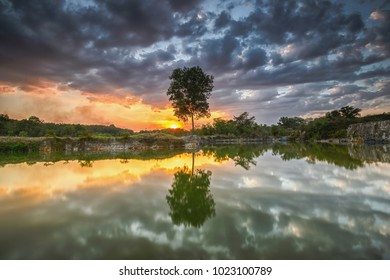 Beautiful sunset reflected on lake, with backlit  tree at Dragon Lake