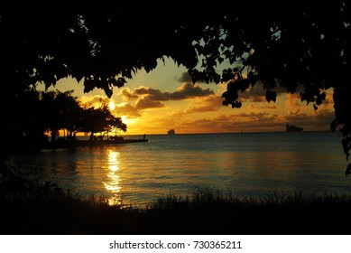 Beautiful sunset reflected in the waters of the Fishing Base in Garapan, Saipan, with silhouettes of the ships in the distance.