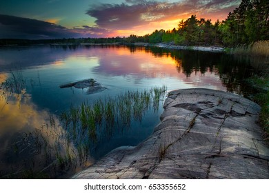 Beautiful sunset with reflection in water. Reeds and a stone beach. Karelia. Ladoga lake.