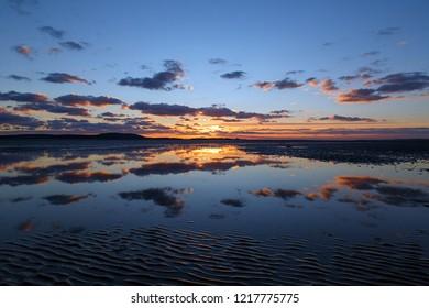 Beautiful sunset reflections on a Gower beach - UK