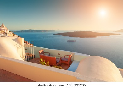Beautiful sunset at Santorini island, Greece. Chairs on the terrace with sea view. Travel destinations concept